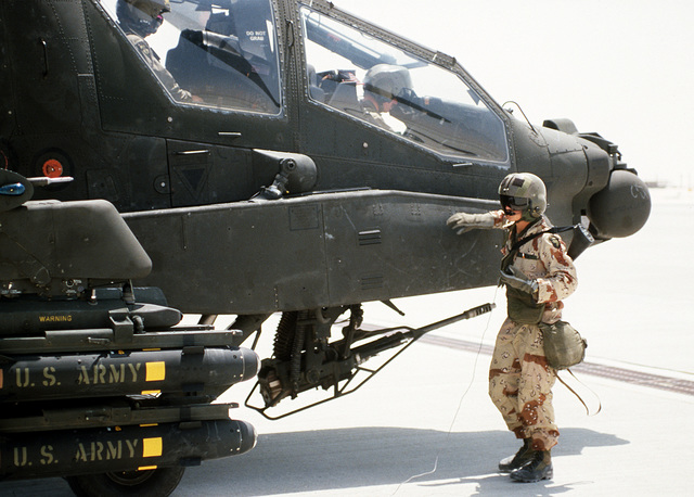 A helicopter crewman from the 101st Airborne Division (Air Assault) stands beside an AH-64A Apache helicopter as it is prepared for takeoff during Operation Desert Shield. The helicopter is armed with an M-230A1 30mm automatic cannon beneath its cockpit and is carrying AGM-114 Hellfire missiles on its wing pylon