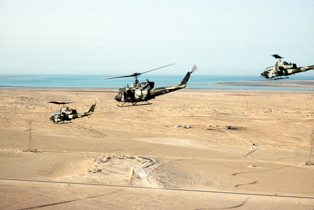 A Marine Corps UH-1N Iroquois helicopter, center, and two AH-1T Sea Cobra helicopters fly near Landing Zone 32 (LZ-32) Site Alpha during Operation Desert Shield