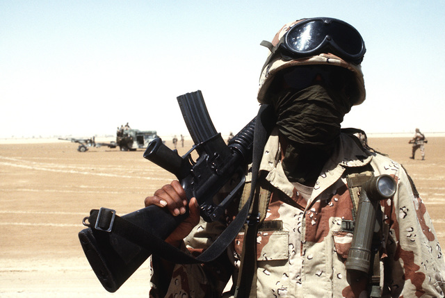 A sergeant with the 82nd Airborne Division wears a kerchief and sunglasses to help protect him from the dust and bright sun of the Saudi desert during Operation Desert Shield. The sergeant is carrying an M-16A2 rifle