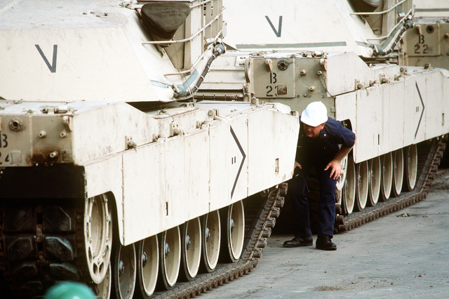 A workman inspect M-1A1 Abrams main battle tanks and M-2 Bradley infantry fighting vehicles on the pier. The 24th Infantry Division equipment is being loaded aboard rapid-response vehicle cargo ships for deployment to Saudi Arabia during Operation Desert Shield