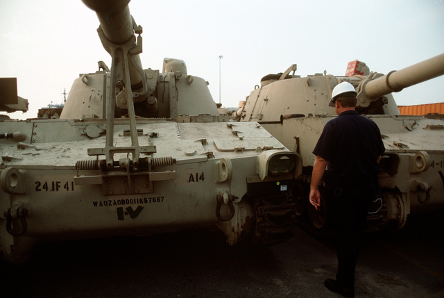 A workman inspects M-109 15mm self-propelled howitzers of the 24th Infantry Division before the guns are loaded onto rapid-response vehicle cargo ships for deployment to Saudi Arabia during Operation Desert Shield