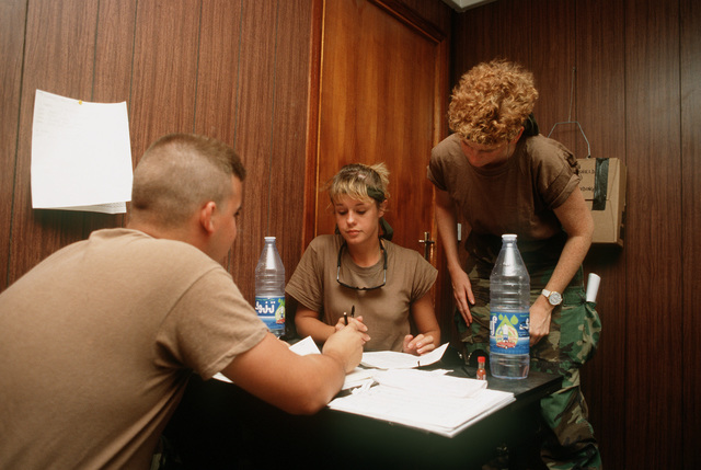 AIRMAN Joe C. Garnero, left, and SGT. Lisa R. Gregson, center, of the 435th Mission Support Squadron discuss administrative matters with AIRMAN 1ST Class Carol J. Stetson of the 37th Tactical Airlift Squadron during Operation Desert Shield