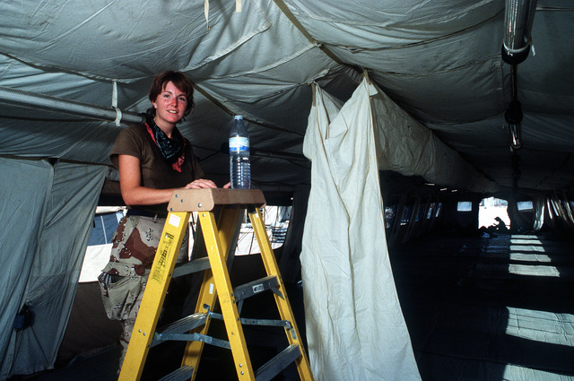An airman stands on a ladder to tie another section of fabric duct to the calling of a tent during Operation Desert Shield
