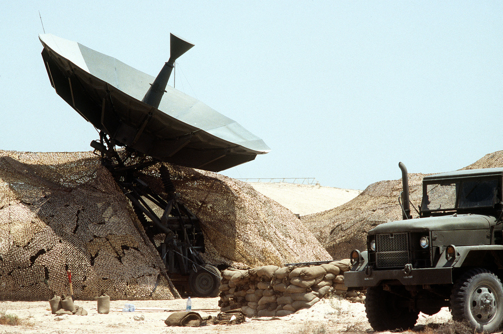 An M-54 5-ton cargo truck sits parked near an antenna at a communications site during Operation Desert Shield