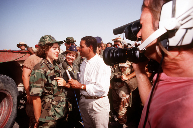 "Bryant Gumble of NBC's ""Today"" show talks with an Air Force captain while on a tour of an air base during Operation Desert Shield"