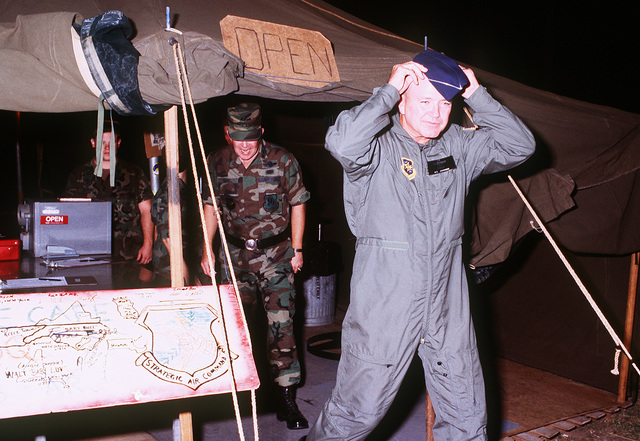 GEN. Hansford T. Johnson, U.S. commander-in-chief, Transportation Command and commander-in-chief, Military Airlift Command, departs from a mess facility while touring U.S. Air Force base camps during Operation Desert Shield. MAJ. GEN. Gerald A. Daniel, commander, 16th Air Force, U.S. Air Forces, Europe, is accompanying Johnson
