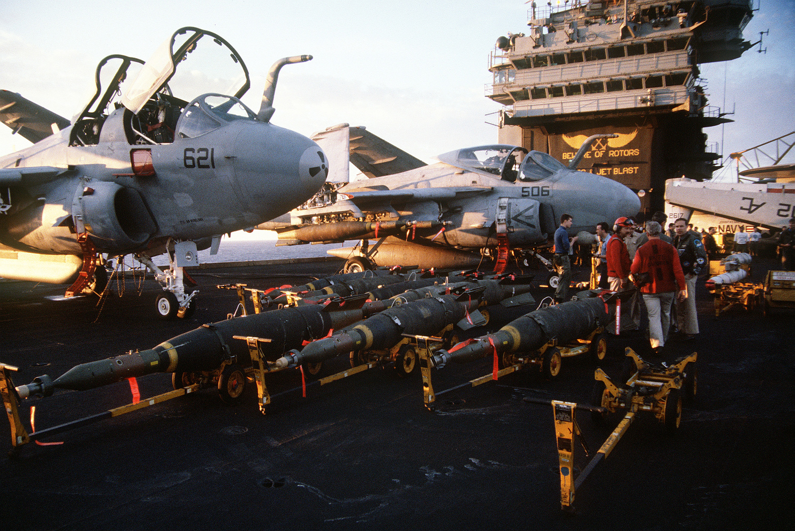 Laser-guided bombs line the flight deck of the aircraft carrier USS JOHN F. KENNEDY (CV-67) in preparation for air strikes against Iraq during Operation Desert Storm. The A-6E Intruder aircraft in the background is armed with laser-guided bombs