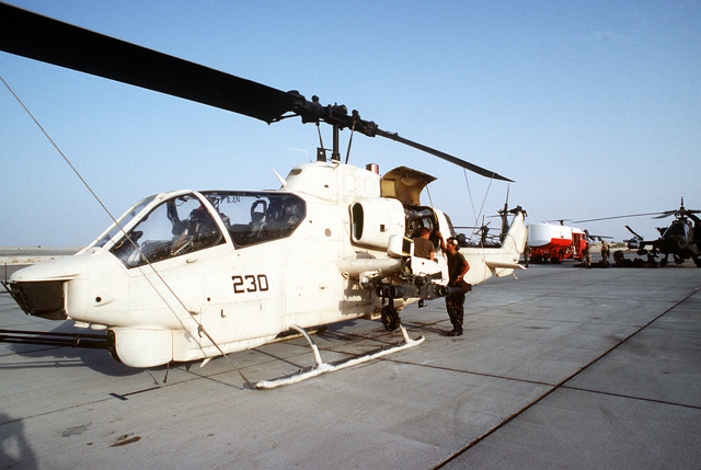 Maintenance crewmen work on an AH-1 Sea Cobra helicopter on the ramp at Landing Zone 32 (LZ-32) Site Alpha during Operation Desert Shield