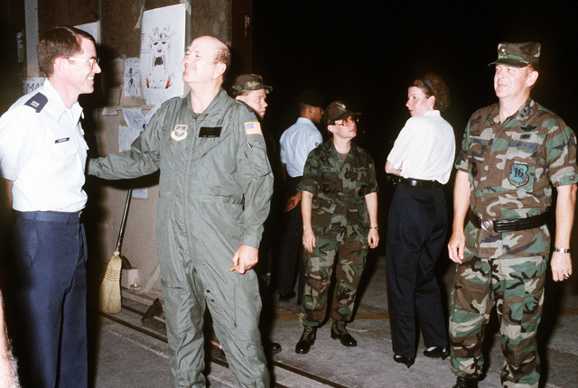 MAJ. GEN. Gerald A. Daniel, commander, 16th Air Force, U.S. Air Forces, Europe, looks on as GEN. Hansford T. Johnson, U.S. commander-in-chief, Transportation Command and commander-in-chief, Military Airlift Command, visits with Air Force personnel during Operation Desert Shield