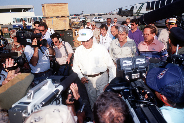 Media personnel crowd around Sen. Robert Dole of Kansas, center, Sen John Warner of Virginia, second from right, and Sen. Sam Nunn of Georgia, right, as they tour a military facility during Operation Desert Shield