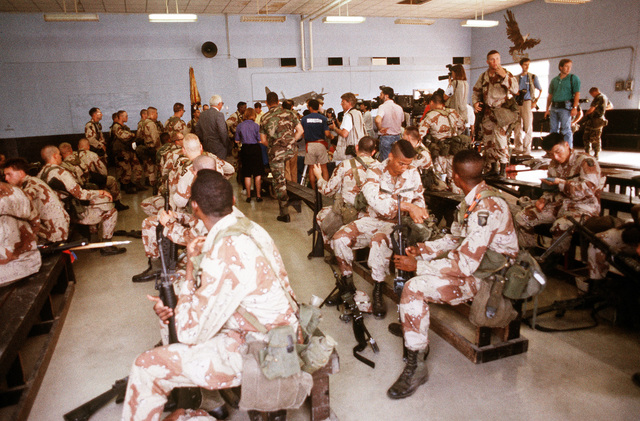 Reporters speak with several soldiers from the 101st Airborne Division (Air Assault) inside a terminal building as other members of the unit wait to board an aircraft to deploy to Saudi Arabia for Operation Desert Shield