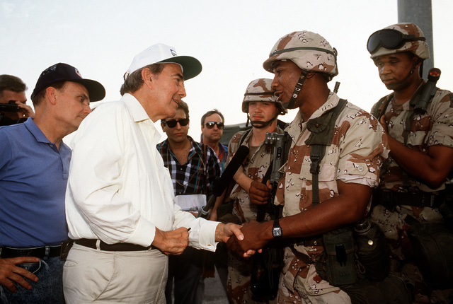 Sen. Robert Dole of Kansas greets a soldier while touring a military facility with other members of a congressional delegation during Operation Desert Shield