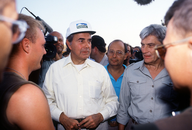 Sen. Robert Dole of Kansas, left, and Sen John Warner of Virginia, right, talk with some of the troops while visiting a military facility during Operation Desert Shield