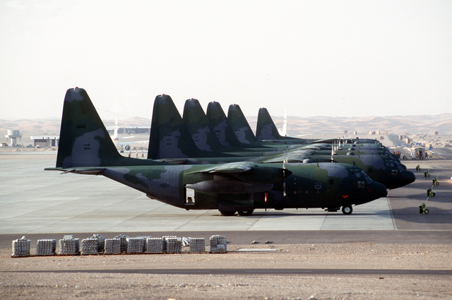 Six C-130 Hercules aircraft sit on the ramp at Landing Zone 32 (LZ-32) Blue during Operation Desert Shield