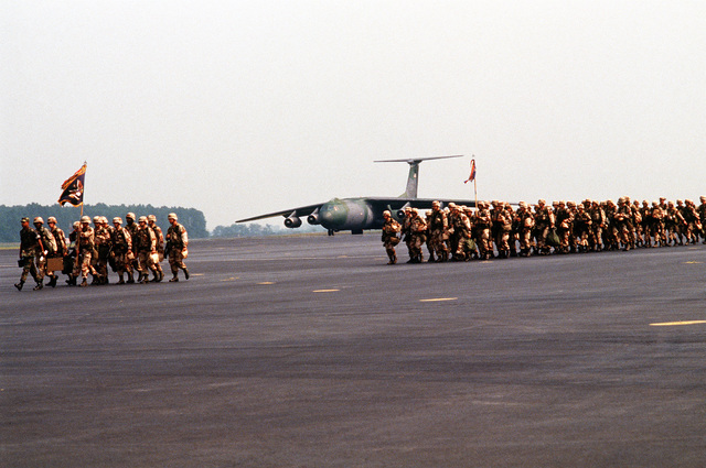 The headquarters staff leads the way as a unit of the 101st Airborne Division (Air Assault) marches across the apron to board the aircraft that will carry them to Saudi Arabia for Operation Desert Shield