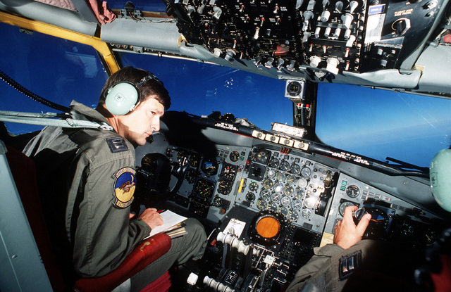 The pilot of a 117th Aerial Refueling Squadron KC-135 Stratotanker aircraft looks out a side window as the aircraft banks into a turn while on a refueling flight during Operation Desert Shield