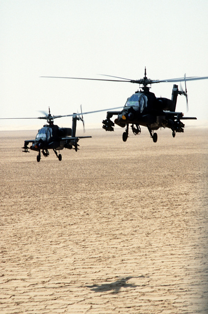 Two AH-64A Apache helicopters pass over the desert during Operation Desert Shield. Each helicopter is armed with a pair of 19-round launchers for 2.75-inch folding-fin aerial rockets; the helicopter at right is also carrying eight AGM-114 Hellfire missiles