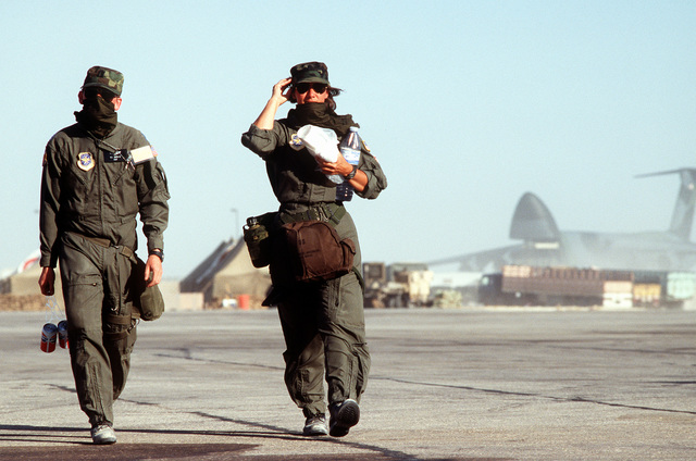 Two Air Force officers, their faces covered for protection against blowing sand, walk across the flight line during Operation Desert Shield