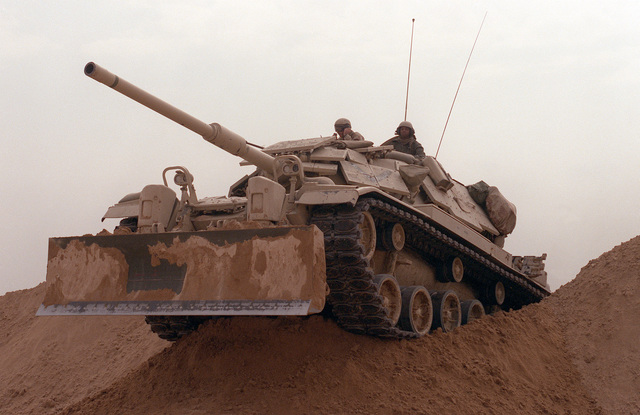 Marines from Company D, 2nd Tank Battalion, drive their M-60A1 main battle tank over a sand berm on Hill 231 while rehearsing their role as part of Task Force Breach Alpha during Operation Desert Storm. The tank is fitted with reactive armor and an M-9 bulldozer kit.