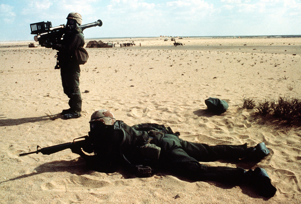 A soldier stands by with a Stinger anti-aircraft guided missile system as his companion sights a target with his M-16A2 rifle during exercise Bright Star '89. Both men are wearing nuclear-biological-chemical warfare gear