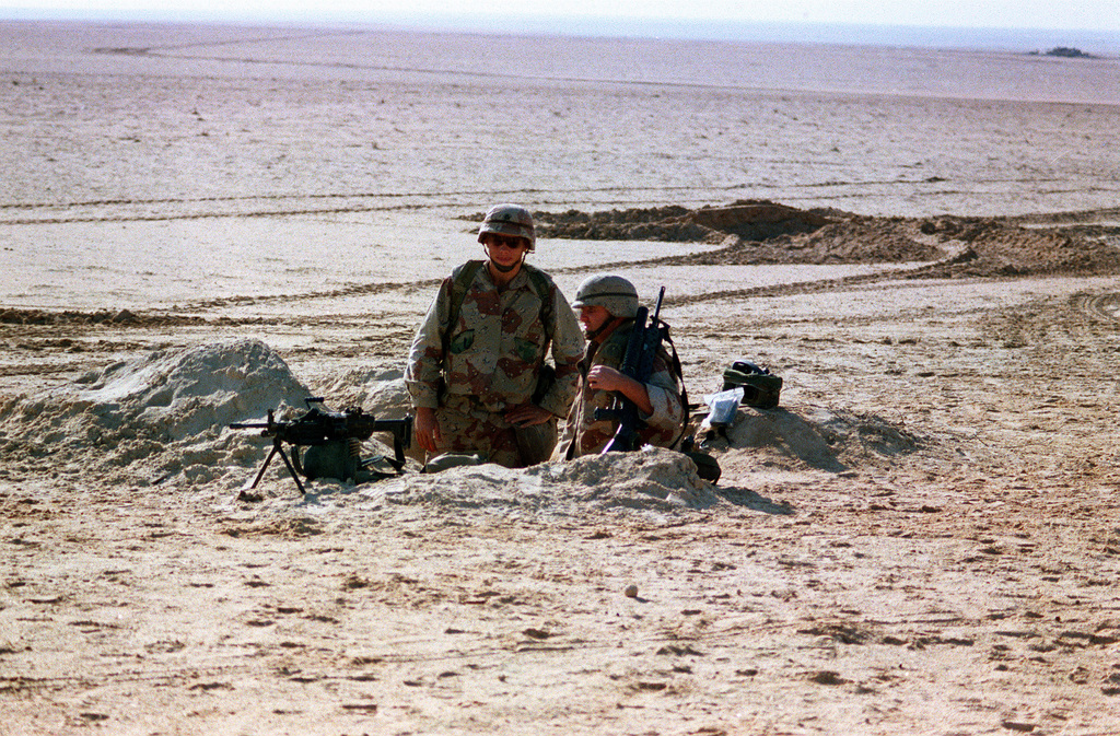 Members of the Tiger Brigade man a foxhole in the desert during Operation Desert Storm. They are armed with an M-249 squad automatic weapon and an M-16A2 rifle equipped with an M-203 grenade launcher