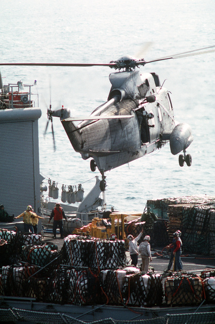 A crewman aboard an SH-3H Sea King helicopter tends the line as several bundles are hoisted into the helicopter from the flight deck of the combat stores ship USS NIAGARA FALLS (AFS-3) during Operation Desert Storm
