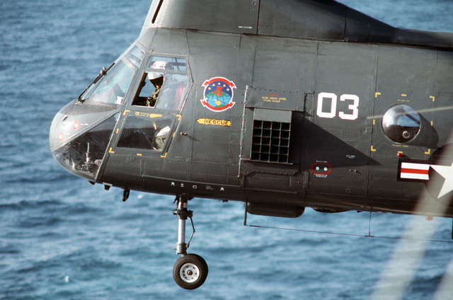 The co-pilot of a Helicopter Combat Support Squadron 5 (HC-5) HH-46A Sea Knight helicopter watches from his side window as the helicopter hovers over a ship while conducting a vertical replenishment during Operation Desert Storm