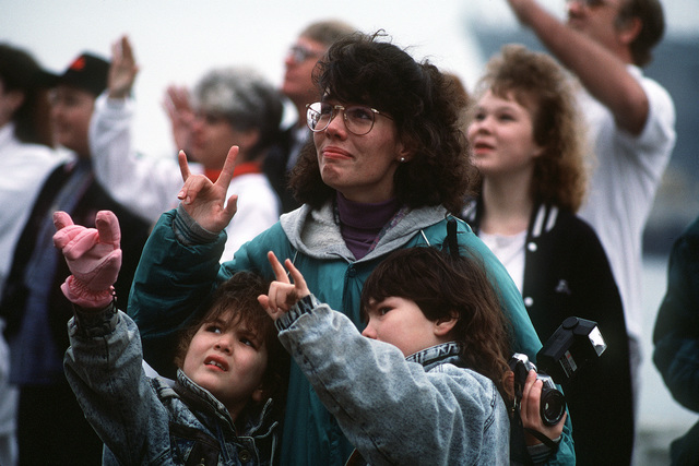 "A woman and two children standing on the pier gesture ""I love you"" to a loved one departing aboard the destroyer tender USS PUGET SOUND (AD-38). The PUGET SOUND is deploying to the Persian Gulf region to support Operation Desert Storm"