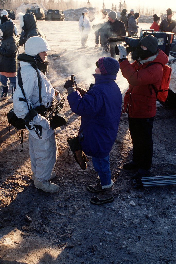 A 6th Infantry Division (Light) soldier carrying an M-249 squad automatic weapon (SAW) is interviewed by a television reporter during the joint readiness exercise Arctic Warrior '91. Members of the news media were invited to observe a live-fire demonstration conducted during the exercise