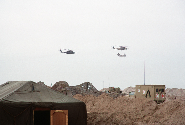 A CH-53E Super Stallion helicopter airlifts a CH-46 Sea Knight helicopter as another CH-53E follows behind. The helicopters have just taken off after a supply delivery during Operation Desert Storm