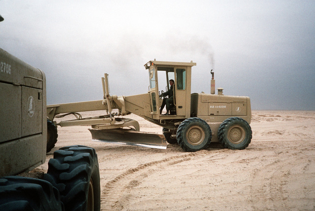 A Seabee drives a John Deere 670 motor grader through a camp being prepared in northern Saudi Arabia during Operation Desert Storm