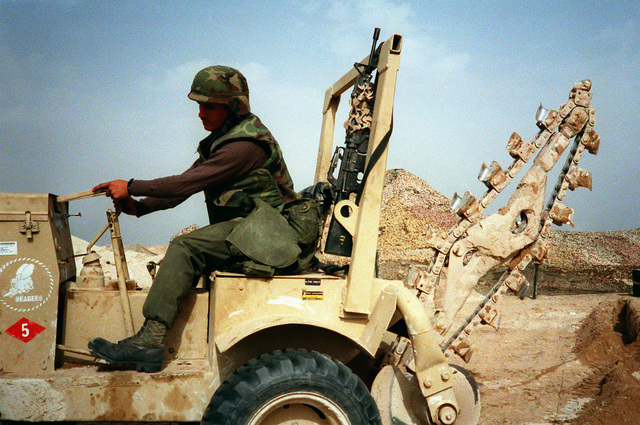 A Seabee from Naval Mobile Construction Battalion 5 (NMCB-5) drives a trench digger to another location after making a path for power cables at a camp under construction in northern Saudi Arabia during Operation Desert Storm