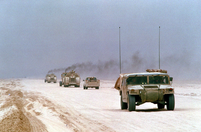 A U.S. Army M998 High-Mobility Multipurpose Wheeled Vehicle (HMMWV), right, drives along a main supply route in northern Saudi Arabia prior to the start of the ground phase of Operation Desert Storm. Two motorized earthmoving scrapers and a utility truck of Naval Mobile Construction Battalion Five (NMCB-5) are driven in the opposite direction in the background