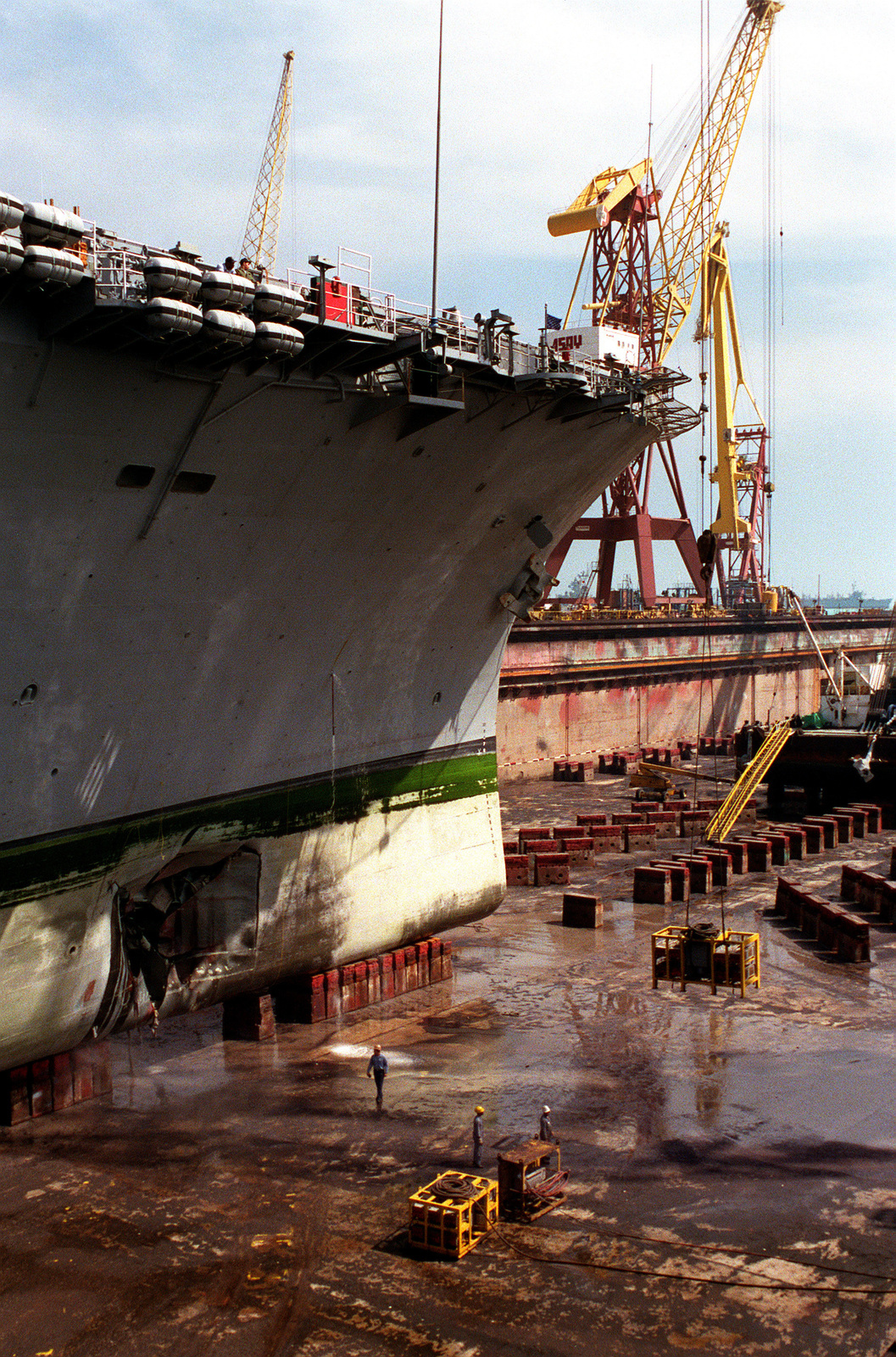A view of the bow of the amphibious assault ship USS TRIPOLI (LPH-10) as the ship lies in dry dock, showing the damage inflicted by an Iraqi mine. The TRIPOLI struck the mine on February 18 while serving as a mine-clearing platform in the northern Persian Gulf during Operation Desert Storm. The ship was able to continue operations after damage control crews stopped the flooding caused by the explosion