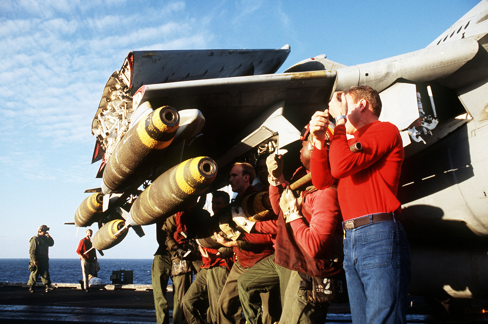 Aviation ordnancemen from Attack Squadron 75 (VA-75) hoist another Mark 82 500-pound bomb up to a multiple ejector rack on the wing of one of their squadron's A-6E Intruder aircraft on the flight deck of the aircraft carrier USS JOHN F. KENNEDY (CV-67) during Operation Desert Storm