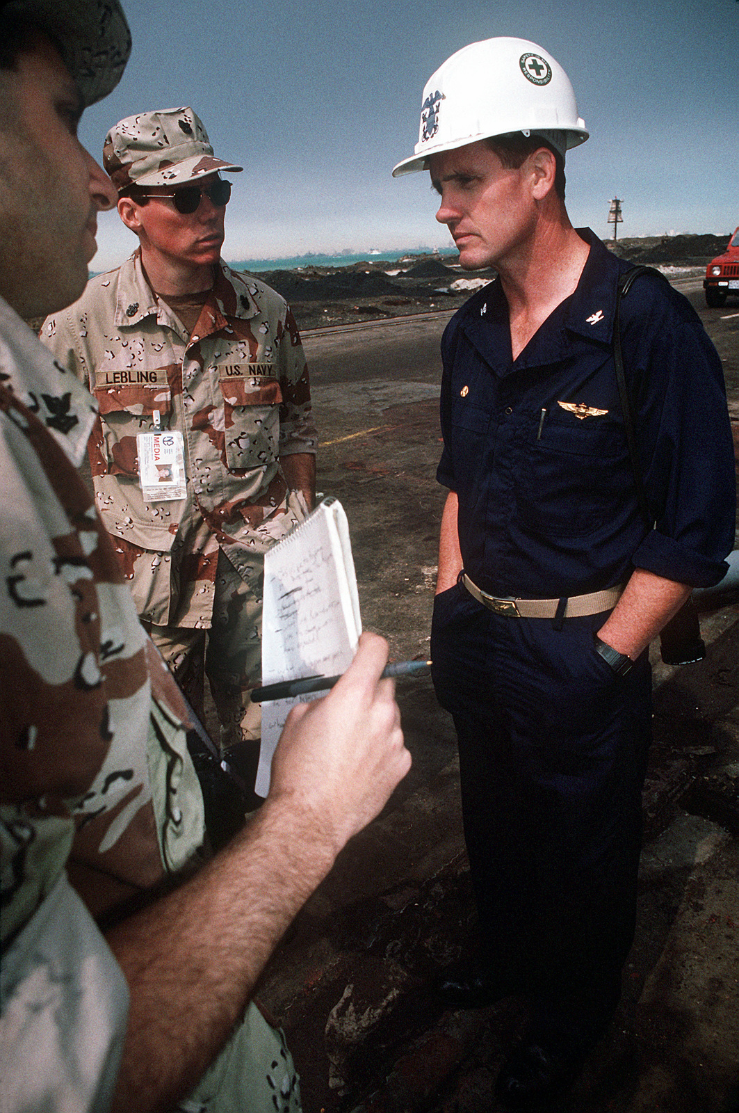 CHIEF PETTY Officer Keith Lebling and Journalist 2nd Class Pete Hatzakos, both of Navy Broadcasting Service, interview CAPT. G.B. McEwen, commanding officer of the amphibious assault ship USS TRIPOLI (LPH-10), regarding damage to the vessel. The TRIPOLI, now in dry dock awaiting repairs, was damaged by an Iraqi mine that the ship struck while serving as a mine-clearing platform in the northern Persian Gulf on February 18 during Operation Desert Storm. The TRIPOLI was able to continue operations after damage control crews stopped the flooding caused by the explosion