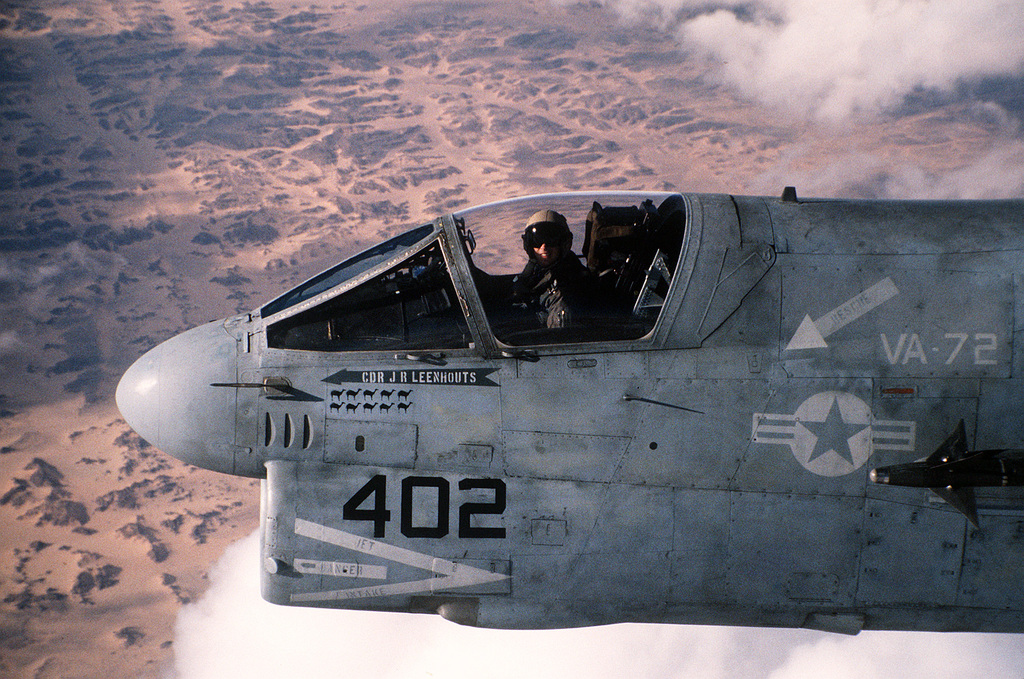 CMDR. John R. Leenhouts, executive officer of Attack Squadron 72 (VA-72), pilots his A-7E Corsair aircraft over the desert on his return flight to the aircraft carrier USS JOHN F. KENNEDY (CV-67) in the Red Sea after a strike on Iraqi targets during Operation Desert Storm. Each camel painted beneath Leenhouts' name on the side of the aircraft represents a strike mission flown during the conflict