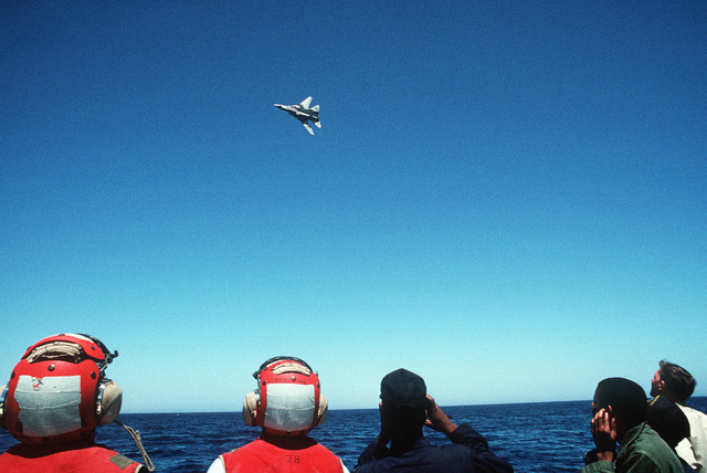 Crew members and U.S. Coast Guardsmen aboard the guided missile destroyer USS WILLIAM V. PRATT (DDG-44) watch as an F-14A Tomcat aircraft of Fighter Squadron 102 (VF-102) flies overhead