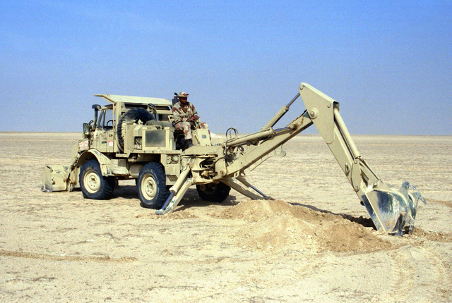 LCPL A.W. Chatman of the 2nd Combat Engineer Battalion operates the backhoe at the rear of a small emplacement excavator (SEE) as he helps dig protective positions for the vehicles and equipment of Task Force Breach Alpha during Operation Desert Storm.