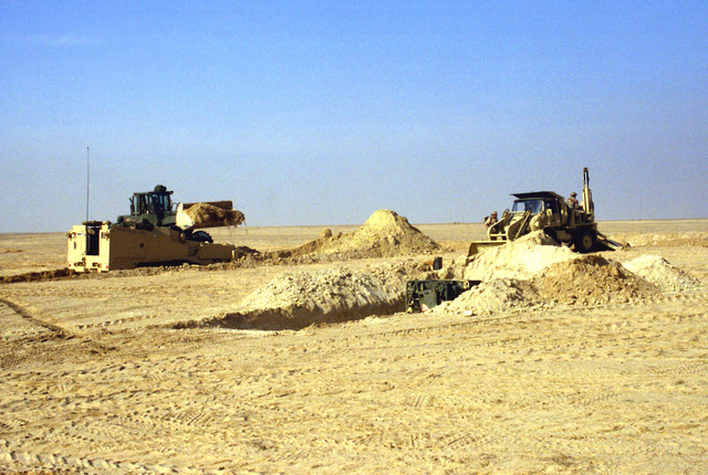 Marines from the 2nd Combat Engineer Battalion use a small emplacement excavator (SEE), right, an M-9 armored combat earthmover (ACE), left foreground, and a front loader to dig protective positions for the vehicles and equipment of Task Force Breach Alpha during Operation Desert Storm.