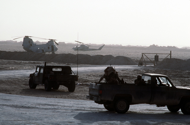One Marine helps another climb into the bed of an M-1008 cargo truck near a landing zone in northern Saudi Arabia during Operation Desert Storm. A CH-46E Sea Knight helicopter, left, and an AH-1T Sea Cobra helicopter are in the background. An M998 High-Mobility Multipurpose Wheeled Vehicle (HMMWV) is in the foreground at left