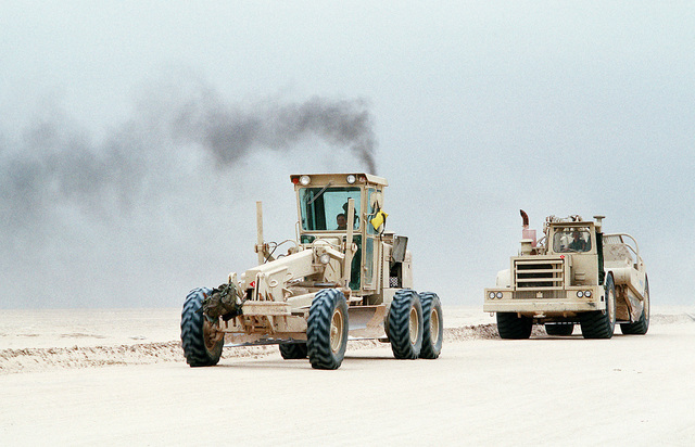 Seabees assigned to Naval Mobile Construction Battalion Five (NMCB-5) drive a John Deere 670 motor grader, left, and a motorized earthmoving scraper along a main supply route in northern Saudi Arabia prior to the start of the ground phase of Operation Desert Storm
