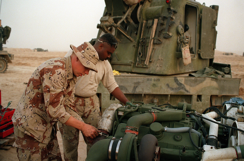 SGT. Bryant, left, and SGT. King of Headquarters Btry., 10th Marines, 2nd Marine Division, work on an engine from an M-109 self-propelled 155mm howitzer during Operation Desert Storm. An M-578 light armored recovery vehicle is behind them.