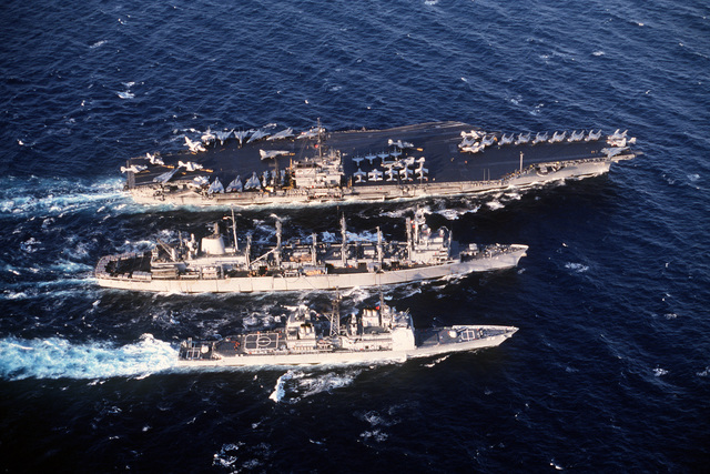 The fast combat support ship USS DETROIT (AOE-4), is flanked by the aircraft carrier USS JOHN F. KENNEDY (CV-67) top, and the guided missile cruiser USS SAN JACINTO (CG-56) as the ships conduct an underway replenishment during Operation Desert Storm