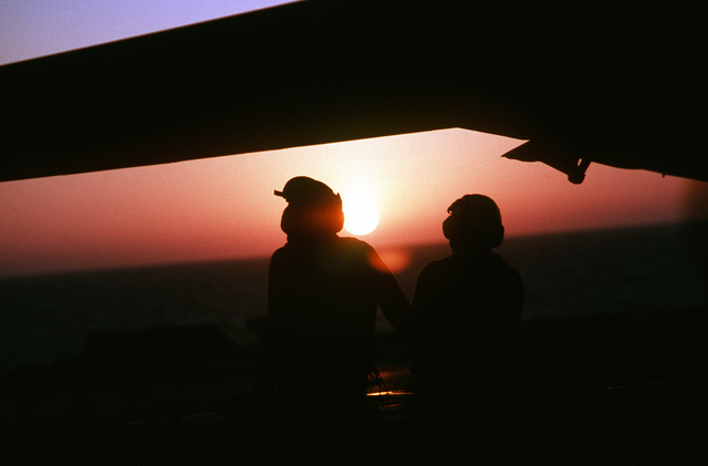 Two flight deck crewmen aboard the aircraft carrier USS SARATOGA (CV-60) are silhouetted against the late afternoon sky during Operation Desert Storm