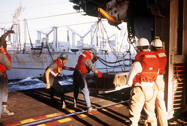 Two sailors aboard the aircraft carrier USS SARATOGA (CV-60) steady a pallet of Mark 82 500-pound bombs that was sent to the ship on a highline rig from a Sacramento class fast combat support ship, background, during Operation Desert Storm
