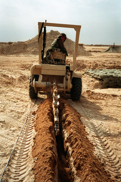 A Seabee from Naval Mobile Construction Battalion 5 (NMCB-5) operates a trench digger to make a path for power cables at a camp under construction in northern Saudi Arabia during Operation Desert Storm