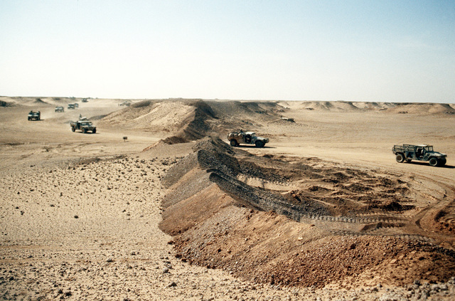 A convoy of M-998 high-mobility, multipurpose, wheeled vehicles drives past a berm as the 4th Battalion, 2nd Brigade move their camp near the border of Iraq during Operation Desert Storm