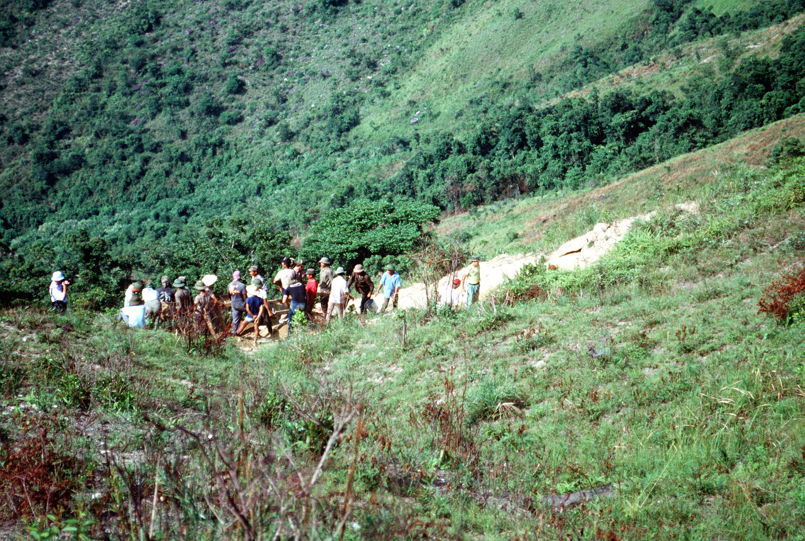 Members of the media as well as representatives of the Joint Combat Casualty Center and members of a joint U.S./Vietnamese anthropological team gather on Dong Nua Mountain, Quang Binh Province, as they discuss search efforts being conducted at the site. The anthropological team is conducting the project in an effort to locate remains of an American pilot whose A-7 Corsair II aircraft crashed while flying a mission during the war in Vietnam.