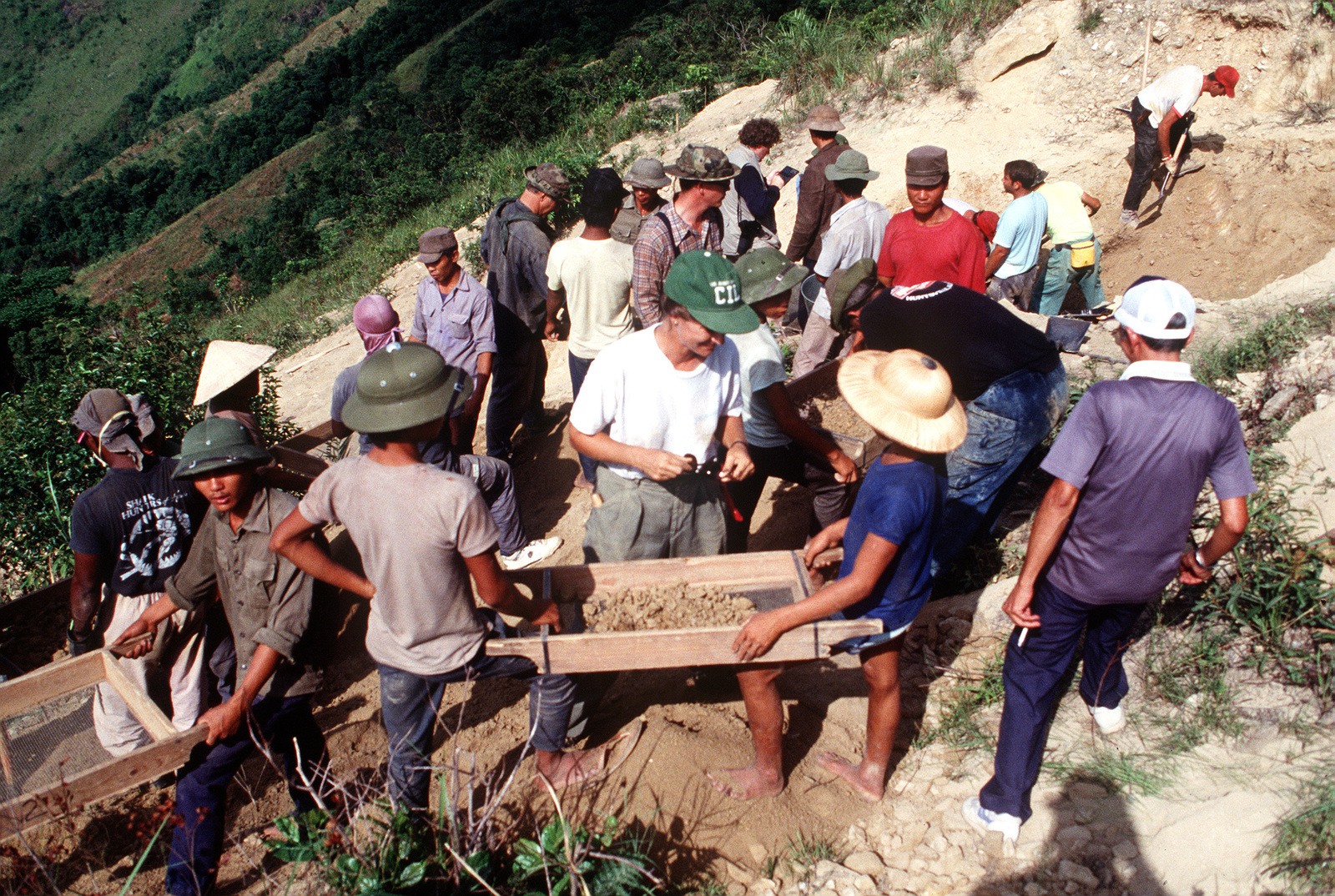 With Joint Combat Casualty Center personnel on hand to gather information, members of a joint U.S./Vietnamese anthropological team prepare to sift through ground and rock fragments in an effort to locate personal effects of an American pilot whose A-7 Corsair II aircraft crashed at the site on Dong Nua Mountain, Quang Binh Province during the war in Vietnam.